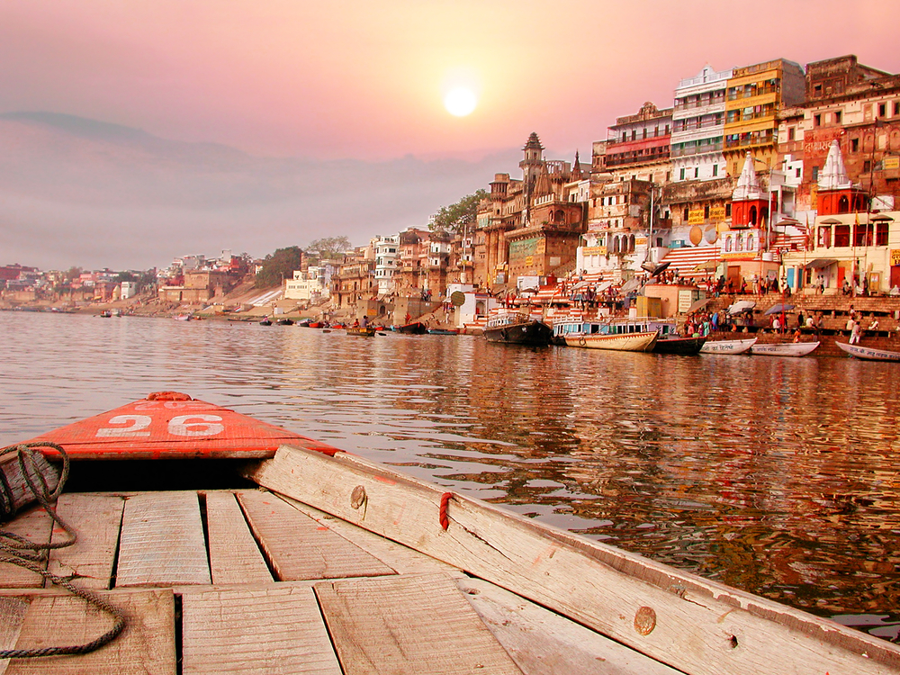 On The Sunset River Bank On The Ganges In India On An Old Wooden Boat